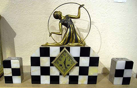 Click here to see more detail of an Art Deco mantel clock with matching garnitures and metal dancer