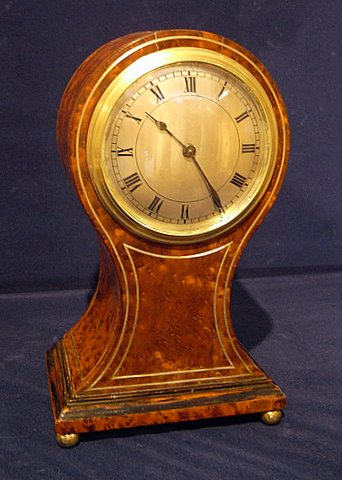 Click here to see more detail of an Edwardian mantel clock in balloon emboyna burl case
