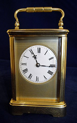 Click here to see more detail of a French brass carriage clock with porcelain dial and Roman numerals