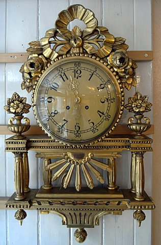 Click here to see more detail of a gilt cartel wall clock