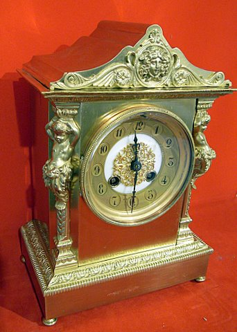 Click here to see more detail of a Victorian mantel clock in an architectural gilded and brass case